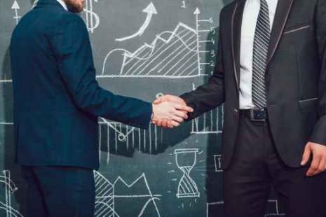 Handshake. Background with charts